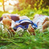 familj ligger i gräset och tar det lugnt