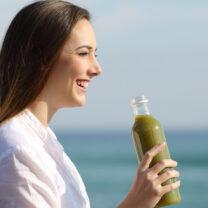 Kvinna dricker grön smoothie vid havet