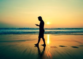 man tittar i sin telefon på stranden