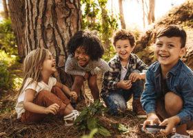 Barn som leker i en skog