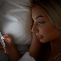 kvinna som tittar på sin mobil i sängen