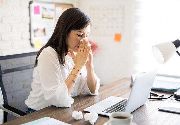 kvinna som är förkyld vid datorn