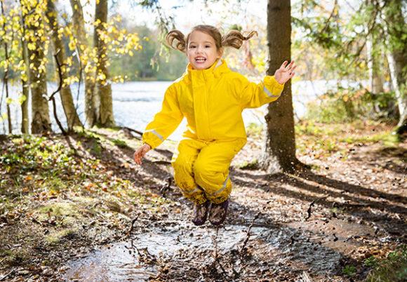 flicka hoppar i vattenpöl
