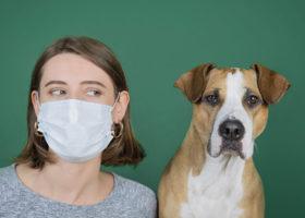Kvinna med ansiktsmask bredvid en hund