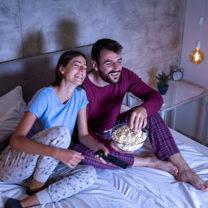 ett par som tittar på tv ihop i sängen