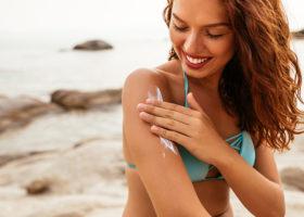 kvinna smörjer in sig med solkräm