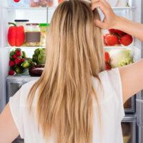 Kvinna tittar in i öppet kylskåp