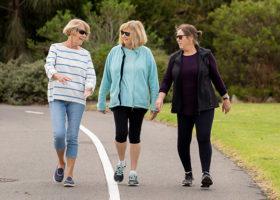 tre kvinnor går efter en väg