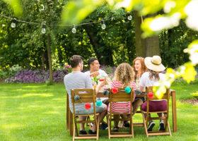 folk sitter i trädgården och äter mat