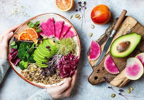 Händer håller i skål med frukt och grönsaker