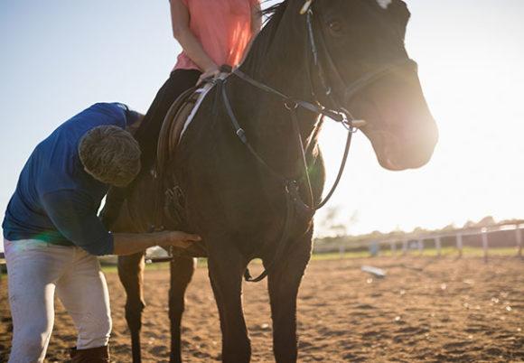 Manlig tränare justerar kvinnas ben i stigbygeln på en på häst