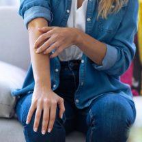 Kvinna sitter i soffa och kliar sig på armen