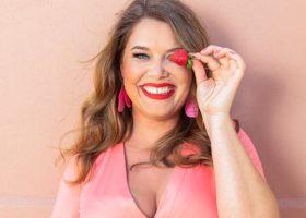 Kocken Jessica Frej i rosa klänning håller en jordgubbe framför ena ögat