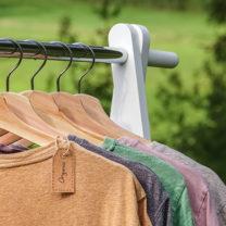 T-shirts hänger i rad i galgar på klädställning utomhus