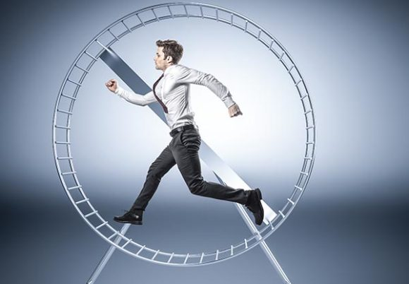 Man i kostym springer i ett hamsterhjul
