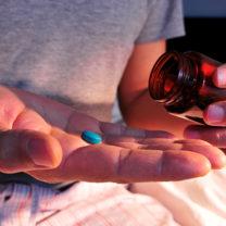 Man i pyjamas sitter på en säng och häett blått piller i handflatan