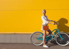 Kvinna som står på en turkos cykel mot en gul vägg