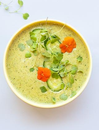 Djup tallrik med grön currysoppa toppad med örter