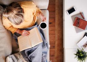 kvinna läser en bok med en kopp kaffe