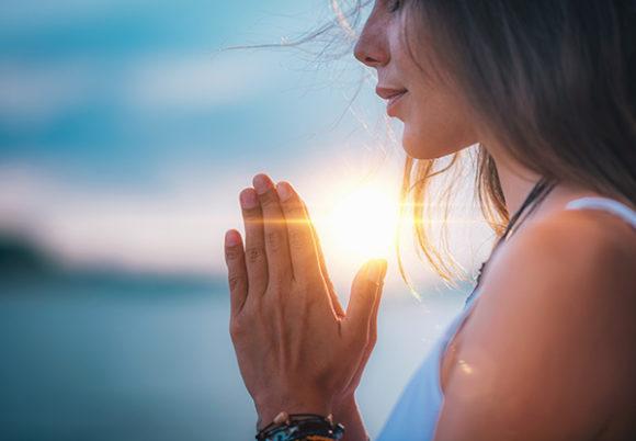 kvinna i profil som sitter i solnedgång och mediterar