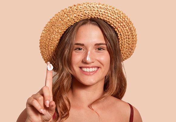 Ung kvinna i solhatt med solskydd på näsan, som håller fram sitt finger med solskydd.