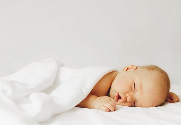 Bebis som sover under vit filt