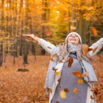 glad kvinna i höstskog