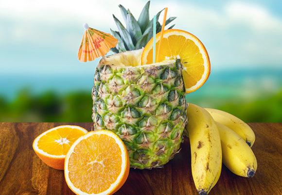 En ananas med sugrör och drinkparaply, bredvid apelsin och bananer