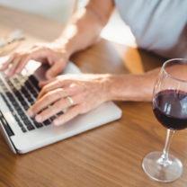 Man skriver på datorn med ett glas rödvin bredvid