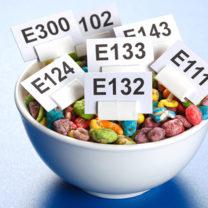 Skål med färgglatt godis med små skyltar nedstuckna med namn på E-nummer