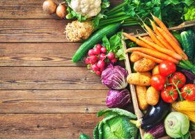 Blandade grönsaker i en låda och på ett bord