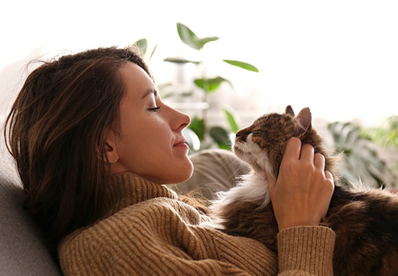 Kvinna sitter i soffa och ser på sin katt i famnen