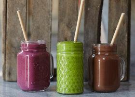 En lila, en grön och en brun smoothie på rad med sugrör i varje.