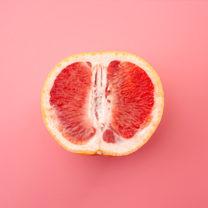 En grapefrukt isolerad på rosa bakgrund, metafor för det kvinnliga könsorganet