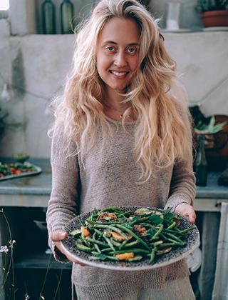 Matkreatören Therese Elgquist håller i en tallrik med grönsaker.