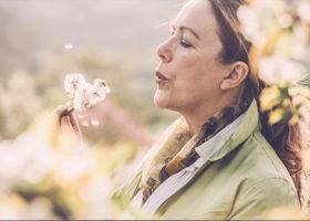 Äldre kvinna blåser på maskrosor