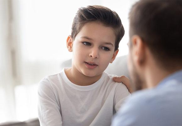 Omtänksam pappa pratar med lille son och visar kärlek och stöd