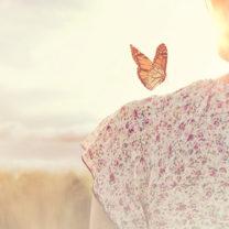 En fjäril sitter på en kvinnas axel. Hon tittar ut över solnedgången