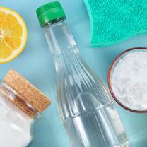 En halv citron, pulver i burkar och en genomskinlig flaska mot turkos bakgrund
