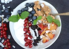 Skål med kokosyoghurt toppad med bär och granola