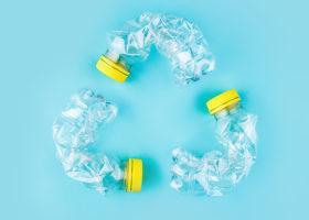 Böjda plastflaskor mot turkos bakgrund som formar trekantig återvinningssymbol