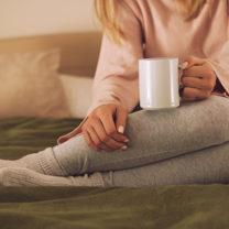 Kvinna sitter i en säng med en kopp i handen