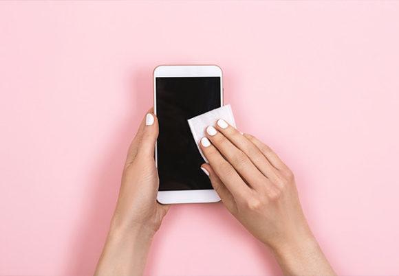 En kvinna desinficerar en smartphone-skärm. Rosa bakgrund.