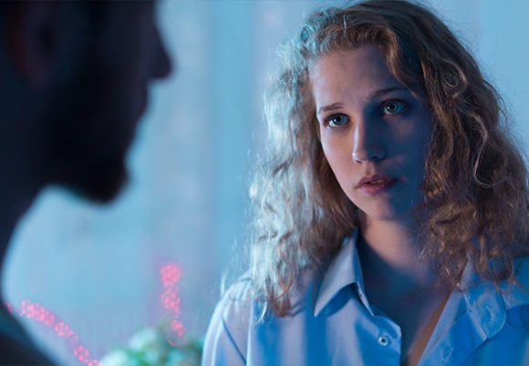 Kvinna i lockigt hår ser bekymrad ut pratar med sin partner, som syns som silhuett
