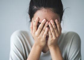 Ung förtvivlad kvinna täcker sitt ansikte med händerna