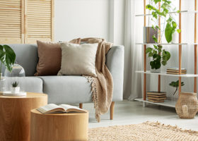 Modernt vardagsrum med soffa och hylla i naturlig, botanisk stil med gröna växter och naturliga material