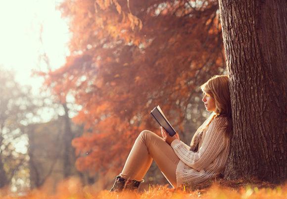 Ung kvinna sitter i en park med fallna höstlöv och läser en bok