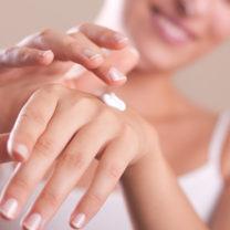 En kvinna smörjer på lotion på sina händer