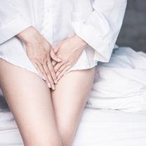 En kvinna i vit skjorta håller handen i grenen, lider av smärta, kliande
