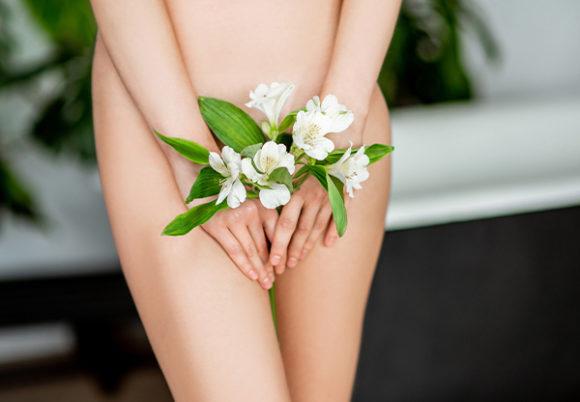 kvinna som håller blommor framför underlivet